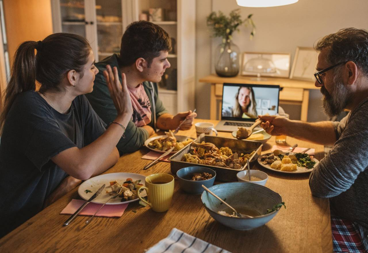 Family sitting at dinner table eating and interacting with a female on a video call shown on laptop